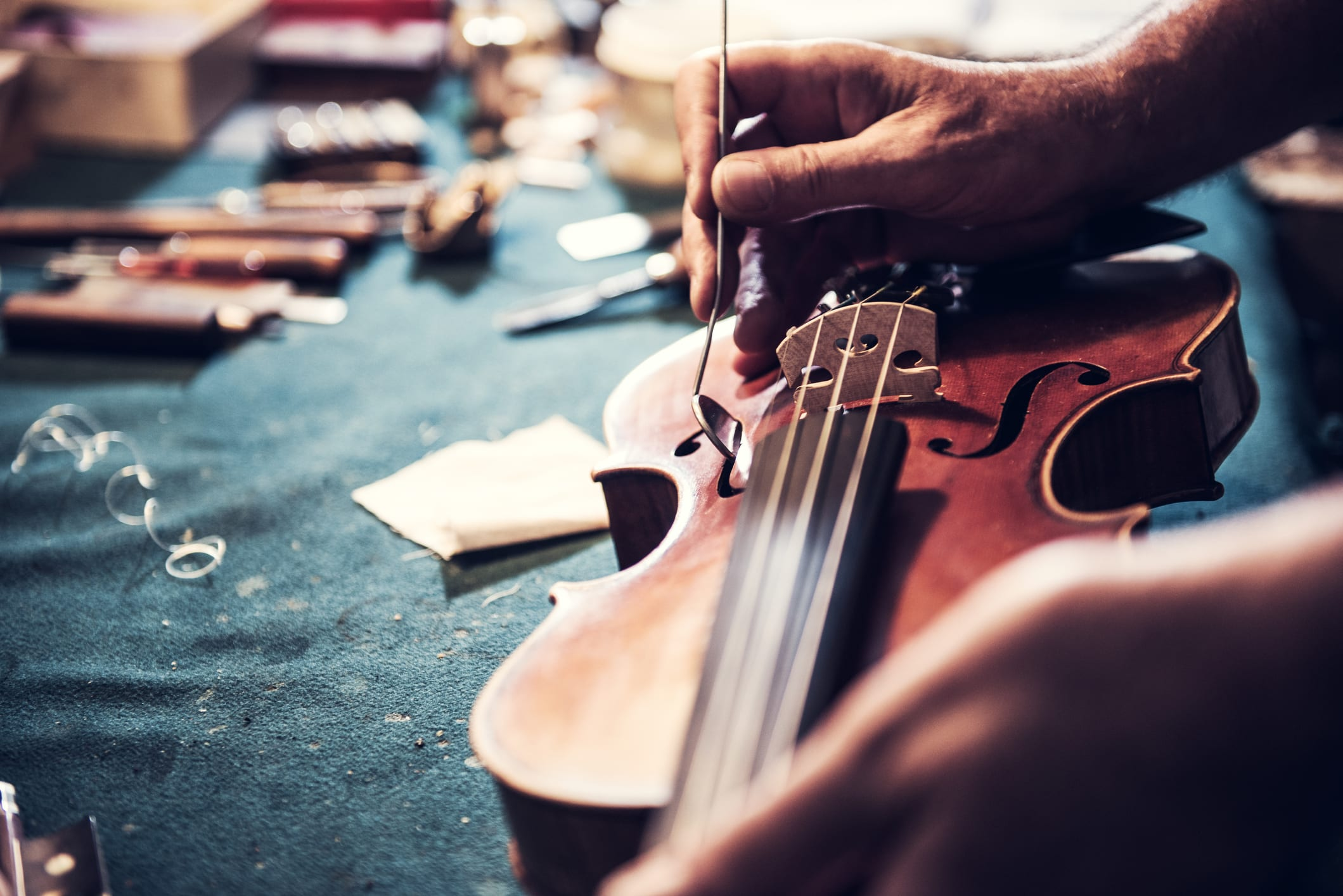 Portrait of senior entrepreneur working in his instrument repair shop, taking care of violins and other music instruments. Experienced senior is using his skills to repair instruments